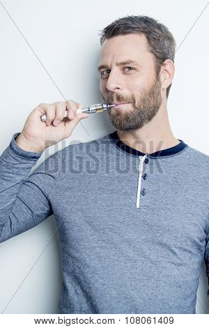 portrait of a young man smoking electric cigarette
