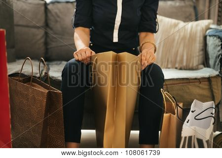 Close Up On Elegant Woman Sitting On Divan With Shopping Bags