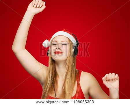 Young Woman In Santa Claus Hat And Headphones Take Pleasure From Music