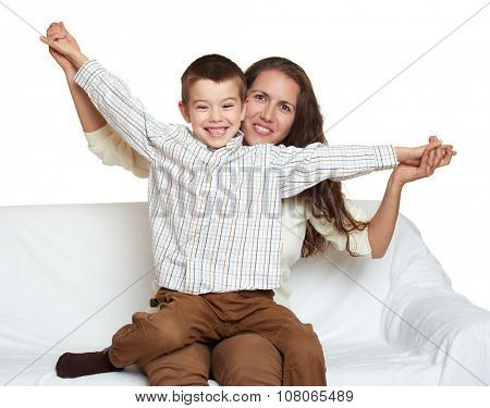 woman with child boy portrait sitting on sofa and playing open arms