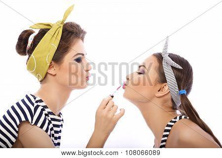 Girl putting lipstick on friend.