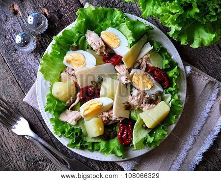salad of lettuce, iceberg lettuce, with canned tuna, dried tomatoes, boiled potatoes, capers and par