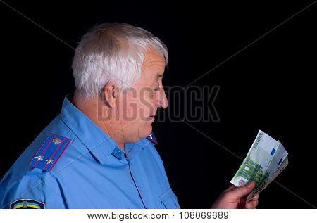 Portrait of police man looking on euro banknotes