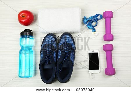 Sport shoes, equipment and smart phone with earphones on light background