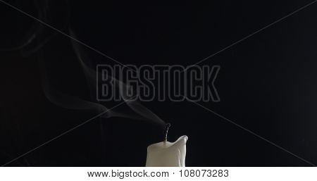 one candle with smoke trail