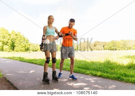 fitness, sport, summer and healthy lifestyle concept - happy couple with roller skates riding outdoors