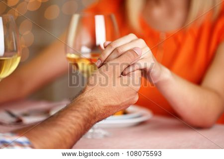 Beautiful woman in orange dress holds man's hand in the restaurant