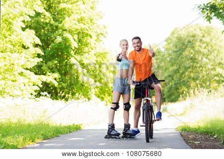 fitness, sport, summer, people and healthy lifestyle concept - happy couple with rollerblades and bicycle showing thumbs up outdoors at summer