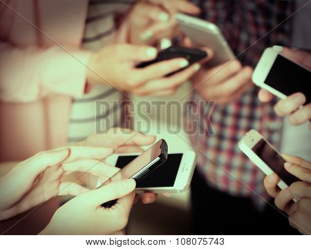 Many hands holding mobile phones close up