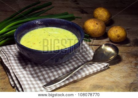 Leek Cream Soup With Fresh Spring Onions And Potatoes On Rustic Wood