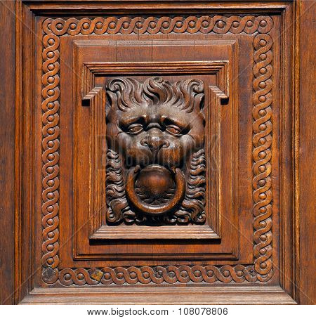 Wooden Lion Cub Holding A Door Handle In His Mouth