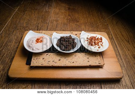 Three different sauces served on a wooden table