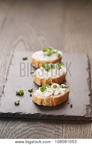 crunchy baguette slices with cream cheese and green onion