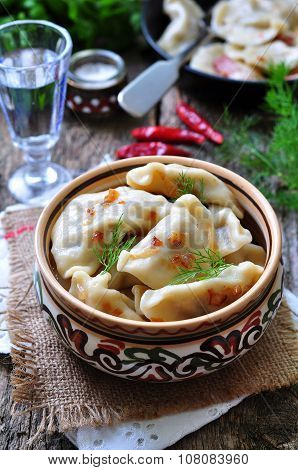 Dumplings with potatoes and mushrooms with fried onions in a traditional ceramic plate on a wooden t