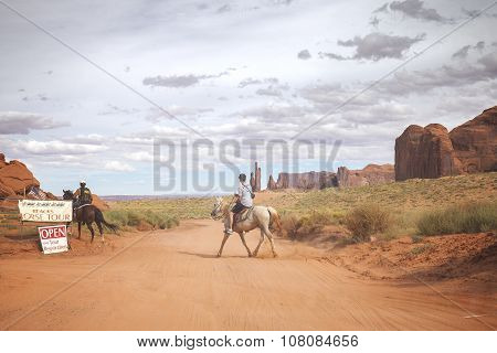 Tourist Riding Horse In Navajo Nation's Monument Valley Park With.