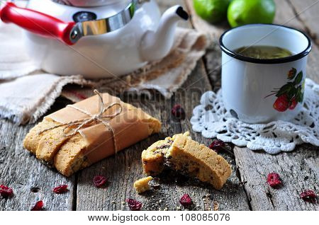 homemade biscotti with dried cranberries and lime, with a cup of green tea kettle on the wooden tabl
