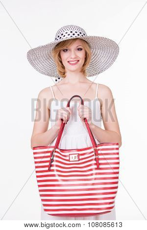 Pretty girl in elegant hat holding red white stripped bag. Smiling fashion woman.
