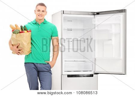 Man with grocery bag standing by an empty fridge isolated on white background