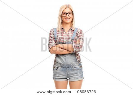 Cheerful hipster girl with black glasses and a short overalls isolated on white background
