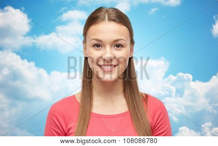 female, gender, portrait, fashion and people concept - smiling young woman or teenage girl in pink pullover over blue sky and clouds background