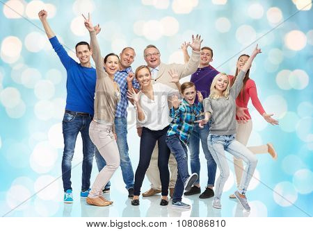 family, gender, generation and people concept - group of smiling men, women and boy having fun and waving hands over blue holidays lights background