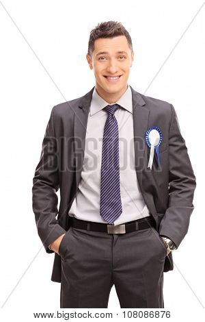Vertical shot of a joyful businessman with a blue award ribbon on his suit isolated on white background