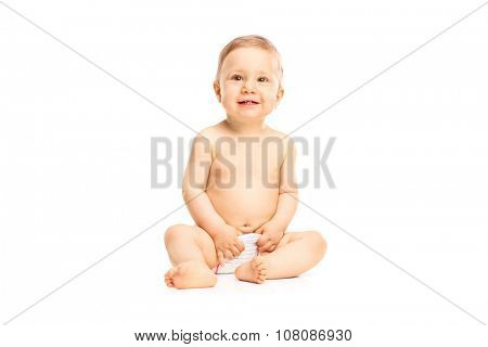 Studio shot of an adorable little baby girl in white diapers smiling and looking up isolated on white background