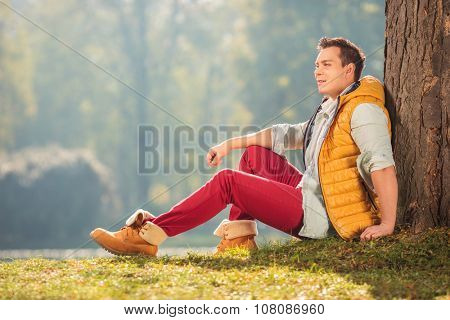 Joyful young man sitting on the grass in a park and leaning against a tree on a beautiful autumn day