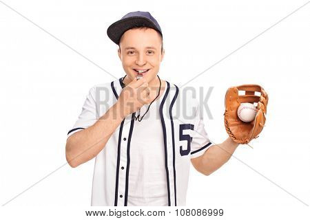 Young baseball coach holding a ball in a baseball glove and blowing a whistle isolated on white background