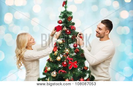 family, x-mas, winter holidays and people concept - happy couple decorating christmas tree over blue holidays lights background