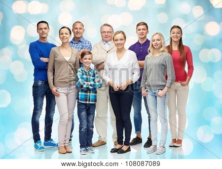 family, gender, generation and people concept - group of smiling men, women and boy over blue holidays lights background