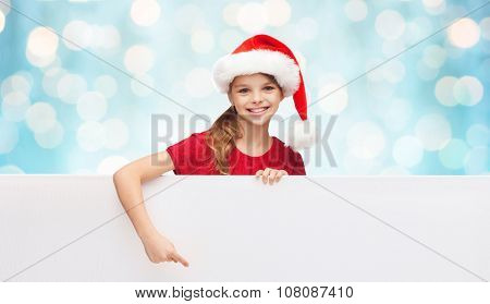 christmas, people, children and advertisement concept - happy girl child in santa helper hat pointing finger on blank white board over blue holidays lights background