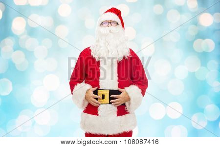 christmas, holidays and people concept - man in costume of santa claus over blue holidays lights background