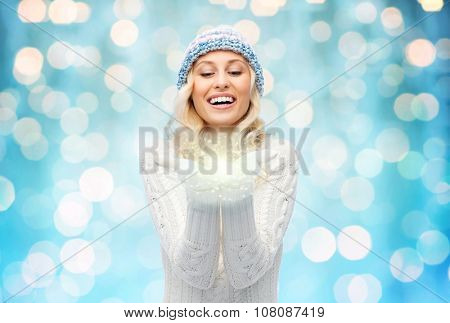 winter, magic, christmas and people concept - smiling young woman in winter hat and sweater holding fairy dust on palms over blue holidays lights background