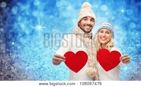 love, valentines day, couple, christmas and people concept - smiling man and woman in winter hats and scarf holding red paper heart shapes over blue glitter or lights background