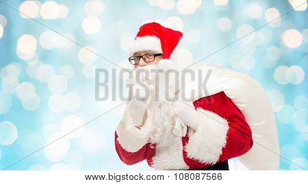 christmas, holidays and people concept - man in costume of santa claus with bag making hush gesture over blue holidays lights background