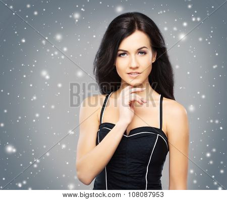 Portrait of the young, beautiful and cute girl with a blowing brunette hair over background with snowflakes.