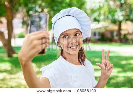 Happy girl in chef's hat making selfie.