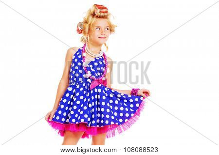 Funny little girl in her mother's hair curlers and polka-dot dress. Kid's fashion, cosmetics. Pin-up style. Isolated over white background.
