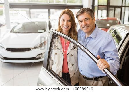 Smiling couple leaning on car at news car showroom