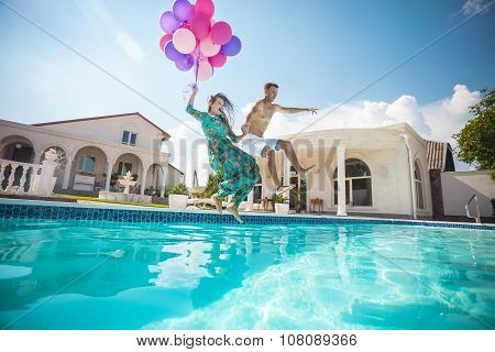 Happy young couple jumping into the pool while holding a bunch of balloons.