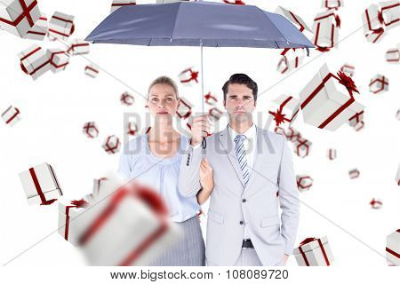 Business people holding a black umbrella against white and red gift box