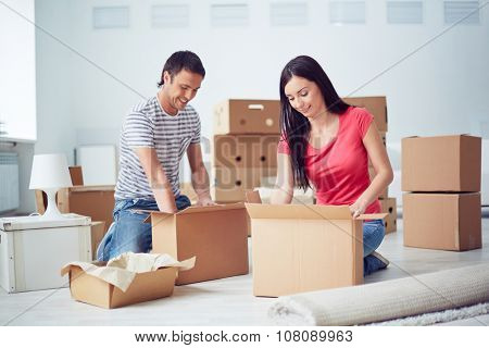 Young couple unpacking boxes in their new home