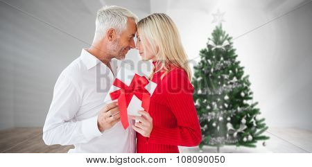 Loving couple with gift against home with christmas tree