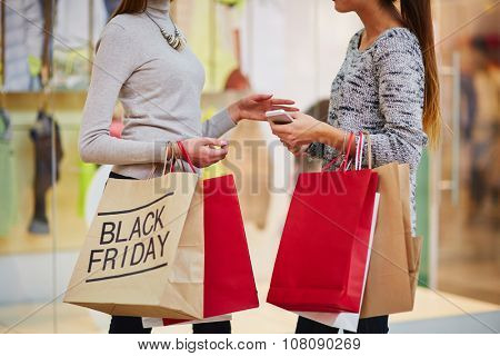 Shopping girls with paperbags talking in the mall