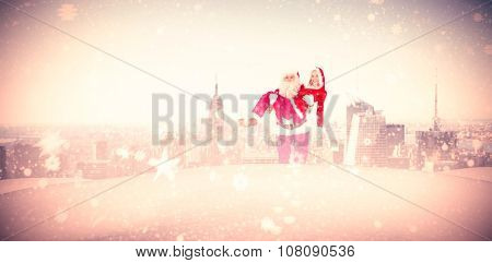 Santa and Mrs Claus smiling at camera against new york skyline