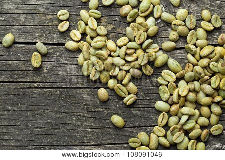 green coffee beans on old wooden background