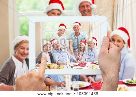 Hand holding tablet pc against happy family in santa hat looking at camera