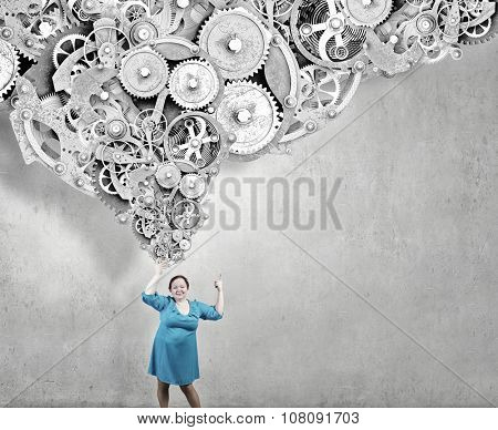 Stout woman of middle age pointing at gears mechanism