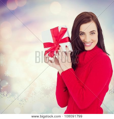 Smiling brunette in red jumper hat showing a gift against glowing christmas background